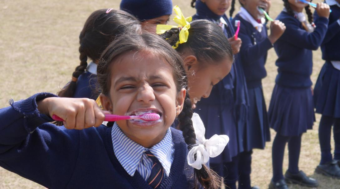 A young girl brushes her teeth during a hygiene workshop in Nepal